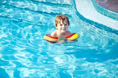 Happy little kid boy having fun in an swimming pool Stock Photography
