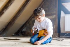 Happy little kid boy helping with toy tools on construction site. Funny child of 7 years having fun on building new stock images
