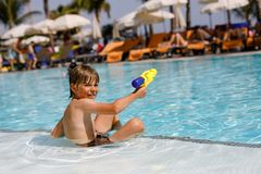 Happy little kid boy jumping in the pool and having fun on family vacations in a hotel resort. Healthy child playing in. Water with a water gun. Laughing royalty free stock photos