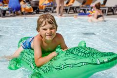 Happy little kid boy jumping in the pool and having fun on family vacations in a hotel resort. Healthy child playing in. Water stock photo