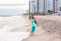 Happy little kid boy and mother having fun on the beach of ocean and on stormy day. Stock Photos