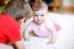 Happy little kid boy with newborn baby girl, cute sister. Siblings. Brother and baby playing together Stock Photos