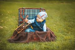 Happy little kid boy playing with airplane toy while sitting in suitcase on green autumn lawn. Children enjoying activity outdoor Royalty Free Stock Photo