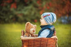 Happy little kid boy playing with bear toy and crying while sitting in basket on green autumn lawn. Children enjoying activity Royalty Free Stock Photography