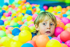Happy little kid boy playing at colorful plastic balls playground high view. Funny child having fun indoors royalty free stock image