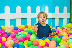 Happy little kid boy playing at colorful plastic balls playground high view. Funny child having fun indoors.  Royalty Free Stock Image