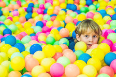 Happy little kid boy playing at colorful plastic balls playground high view. Funny child having fun indoors.  Stock Images