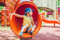 Happy little kid boy playing at colorful playground. Adorable child having fun outdoors.  Stock Photo