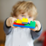 Happy little kid boy playing with construction blocks with creat Stock Photos