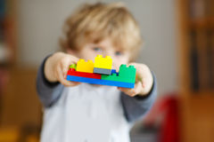 Happy little kid boy playing with construction blocks with creat Royalty Free Stock Image