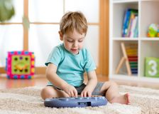 Happy little kid boy playing piano toy royalty free stock photo