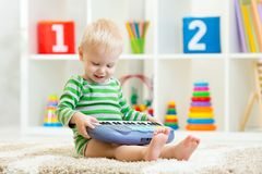 Happy little kid boy playing piano toy Stock Photo