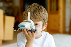 Happy little kid boy playing with space shuttle toy. Cute child in having fun in the morning before school. Closeup of face and old toy Stock Photography