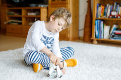 Happy little kid boy playing with space shuttle toy. Cute child in pajamas having fun in the morning before school Stock Images