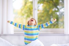 Happy little kid boy after sleeping in bed in colorful nightwear Stock Photos