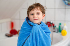 Happy little kid boy after taking bath with blue towel. Happy little kid boy after taking bath wet and smiling. Adorable child with blond hairs taking bath and Royalty Free Stock Photography