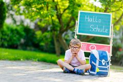 Free Happy Little Kid Boy With Glasses Sitting By Desk And Backpack Or Satchel. Schoolkid With Traditional German School Bag Royalty Free Stock Photo - 124725555