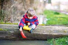 Happy little kid boy in yellow rain boots playing with paper ship boat by huge puddle on spring or autumn day. Active leisure for children. Funny child having Stock Photo
