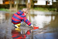 Happy little kid boy in yellow rain boots playing with paper ship boat by huge puddle on spring or autumn day. Active. Leisure for children. Funny child having royalty free stock photos
