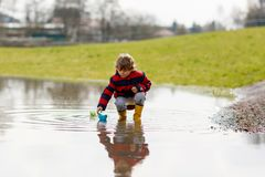 Happy little kid boy in yellow rain boots playing with paper ship boat by huge puddle on spring or autumn day. Active. Leisure for children. Funny child having stock images