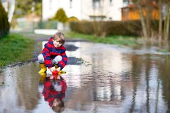 Happy little kid boy in yellow rain boots playing with paper ship boat by huge puddle on spring or autumn day. Active. Leisure for children. Funny child having stock photos