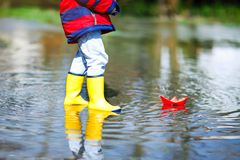 Happy little kid boy in yellow rain boots playing with paper ship boat by huge puddle on spring or autumn day. Active leisure for children. Funny child having royalty free stock images