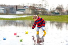 Happy little kid boy in yellow rain boots playing with paper ship boat by huge puddle on spring or autumn day. Active leisure for children. Funny child having royalty free stock photography