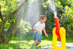 Little kid boy playing  with a garden hose and water Stock Image