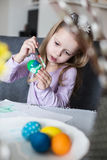 A happy little kid coloring easter eggs Royalty Free Stock Photography