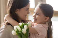 Happy kid daughter embracing mom receiving tulips on mothers day. Happy little kid daughter embracing looking at smiling mom receiving tulips flowers bouquet stock images