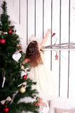 Happy little kid decorate the Christmas tree and home. Stock Photo