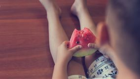 Happy little kid eating watermelon indoors. Toned image. royalty free stock images