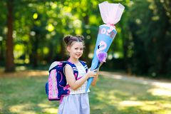 Happy little kid girl with backpack or satchel and big school bag or cone traditional in Germany for the first day of royalty free stock photos