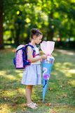 Happy little kid girl with backpack or satchel and big school bag or cone traditional in Germany for the first day of royalty free stock photography