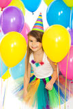 Happy little kid girl with colorful balloons on