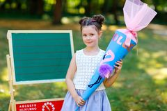 Happy little kid girl by desk with backpack or satchel and big school bag or cone traditional in Germany for the first royalty free stock images