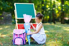 Happy little kid girl by desk with backpack or satchel and big school bag or cone traditional in Germany for the first stock photo