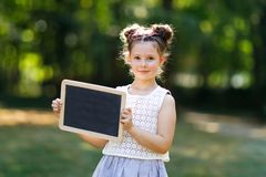 Happy little kid girl holding empty chalk desk in hands. Schoolkid on first day of elementary class. Healthy adorable. Child outdoors, in green park. Copyspace stock photos