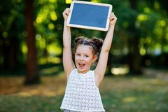 Happy little kid girl holding empty chalk desk in hands. Schoolkid on first day of elementary class. Healthy adorable royalty free stock images