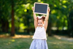Happy little kid girl holding empty chalk desk in hands. Schoolkid on first day of elementary class. Healthy adorable. Child outdoors, in green park. Copyspace royalty free stock photos
