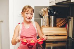 Happy little kid girl holding tray of freshly baked muffins. Cooking with children stock images