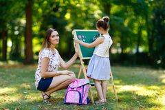 Happy little kid girl and mother by big chalk desk Preschool or schoolkid on first day of elementary class. Back to. School concept. Healthy child and women stock photo