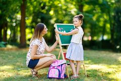 Happy little kid girl and mother by big chalk desk Preschool or schoolkid on first day of elementary class. Back to royalty free stock image