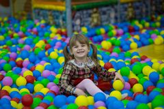 Happy little kid girl in red dress play in pool with colorful plastic balls. Funny child having fun indoors Stock Image