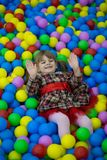 Happy little kid girl in red dress play in pool with colorful plastic balls. Funny child having fun indoors Stock Photography