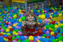 Happy little kid girl in red dress play in pool with colorful plastic balls. Funny child having fun indoors Royalty Free Stock Photography
