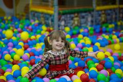 Happy little kid girl in red dress play in pool with colorful plastic balls. Funny child having fun indoors Stock Photo
