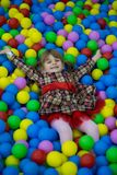 Happy little kid girl in red dress play in pool with colorful plastic balls stock photography