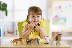 Happy little kid girl. Smiling child toddler plays animal toys at home or kindergarten royalty free stock photos