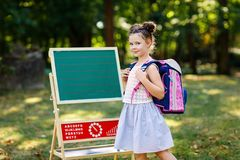 Happy little kid girl standing by desk with backpack or satchel. Schoolkid on first day of elementary class. Back to. School concept. Healthy adorable child stock image
